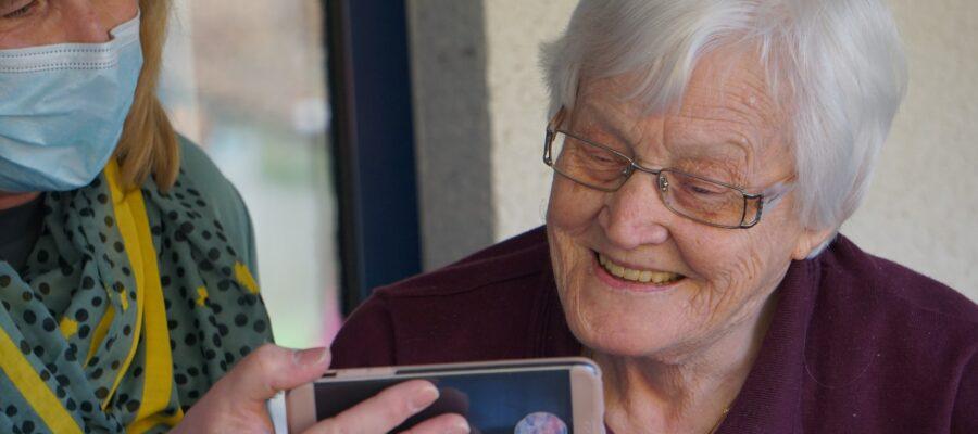 Blick auf eine ältere Frau mit Tochter und Smartphone